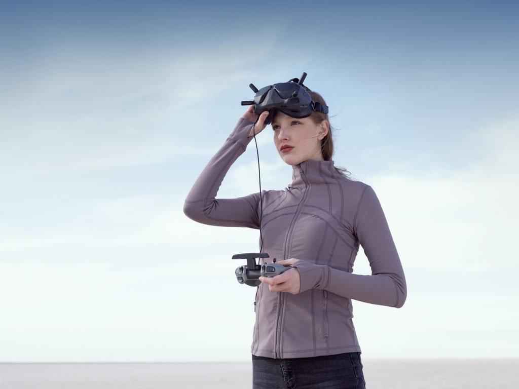 Woman flying DJI Drone with goggles and controller